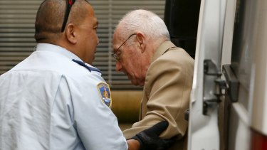 A correctional officer escorts Roger Rogerson to court for his murder trial last week.