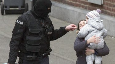Police evacuate a woman and a small child during a police raid targeting Paris attacks suspect Salah Abdeslam.