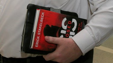 Coalition MP George Christensen, a keen purchaser of books on Islamic State, arrives at Canberra airport earlier this year carrying the book 'ISIS Exposed' by Erick Stakelbeck.