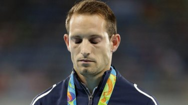 France's Renaud Lavillenie stands on the podium with his silver medal during the medals ceremony for the men's pole vault in Rio, while the crowd boos.