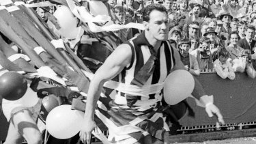 Ray Gabelich leads the Collingwood team onto the ground in the 1964 grand final.