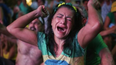 A pro-impeachment supporter dressed in Brazilian national colours cheers as a 'Yes' vote is cast in the lower house.