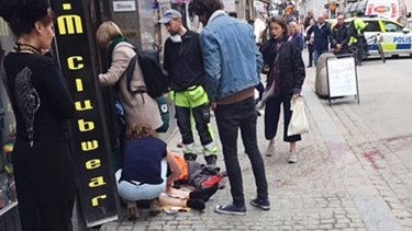 An injured person is helped by passers-by.