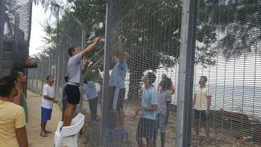 Refugees securing a recently damaged perimeter fence at the Manus Island immigration detention centre on October 30.