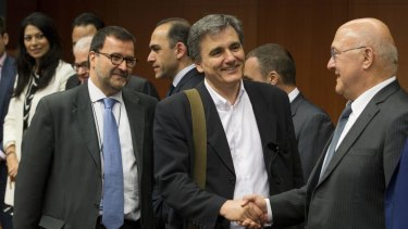 French Finance Minister Michel Sapin (right) shakes hands with his Greek counterpart Euclid Tsakalotos at a Eurogroup meeting in Brussels on Monday.