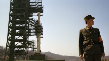 In this April 8, 2012 photo, a North Korean soldier stands guard in front of the country's Unha-3 rocket at Sohae Satellite Station in Tongchang-ri, North Korea.