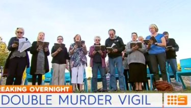 Community members pray for the children at a vigil.