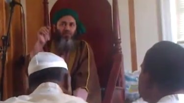 Alauddin Akhonji (in green turban) addresses worshippers at al-Furqan mosque in New York, in a video posted in September 2013.