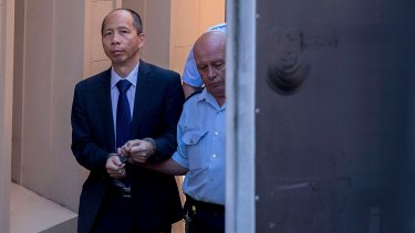 Robert Xie is escorted to a prison truck after being found guilty of the murder of the Lin family.