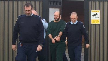 Marcus Standford is escorted from Leeton police station to the court house.