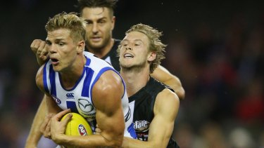 Mason Wood of the Kangaroos marks the ball against Jimmy Webster of the Saints.