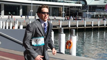 Sydney lawyer Matthew Whitaker, 25, ran the 42-kilometre Sydney Running Festival dressed in a suit – and broke a Guinness World Record.