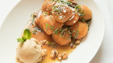 Loukoumades doused in a sugar syrup, along with a scoop of salted caramel ice cream.