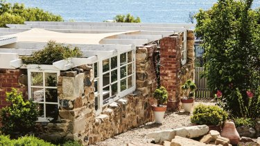 The sandstone cottage on the shore of Clarks Bay, with its outdoor entertaining area, owes its new lease of life to the efforts of Sarah and Phil Webb.