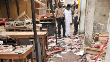 Rescue workers inspect the scene of Kano market explosion, Nigeria. .