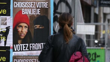 """Posters for far right anti-immigration party National Front state """"Choose your suburbs Vote Front!"""" in Paris this month."""