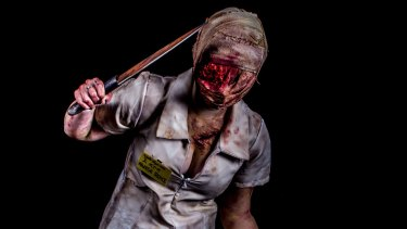 A fan imitates the nurse from the Silent Hill video game and horror movie after a makeover from special effects artist Kel McQueen.