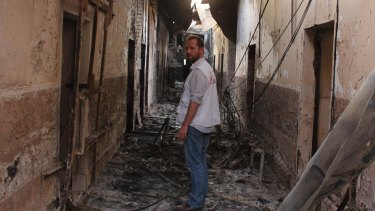 An employee of the Doctors Without Borders in the charred remains of the hospital earlier this month after it was hit by a US airstrike.