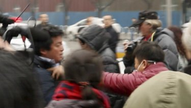 A plain-clothes policeman (in red jacket) seizes Fairfax Media's China Correspondent Philip Wen outside the courthouse.