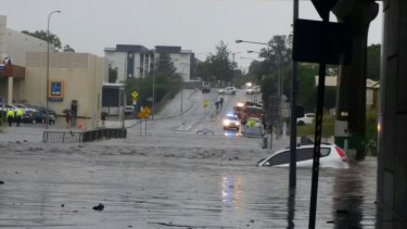 A small hatchback is swept away by flooding in suburban Brisbane.