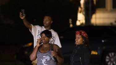 Bystanders watch as a crowd gathers following the fatal shooting of a man in Milwaukee.