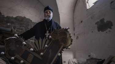 Father Andreus Tamer displays smashed crosses and icons.