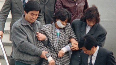 In this 1987 photo, Kim Hyon-hui, with her mouth taped, is taken out from a plane upon her arrival in Seoul,