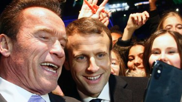 French President Emmanuel Macron, centre, and former California governor Arnold Schwarzenegger take a selfie in Paris on Tuesday.
