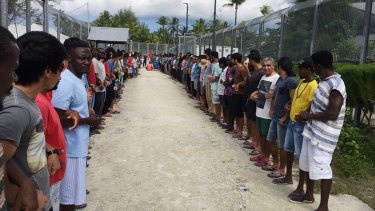 Refugees at Manus Island detention centre link hands in solidarity before the centre's closure this week.