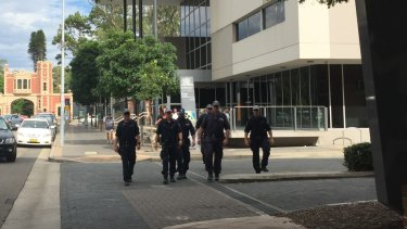 Armed police officers leave Parramatta Children's Court following the February court appearance of two teenagers charged with terrorism offences.