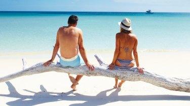 A couple enjoy the beach and vista at Lizard Island.