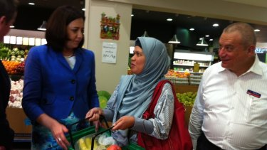 Opposition Leader Annastacia Palaszczuk talks about a possible GST on fresh fruit with Arya Putri from Kuraby at Sumnybank Hills Shopping Centre. Labor's Sunnybank candidate, lawyer Peter Russo, watches on.