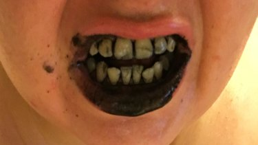 Catherine Bouris using charcoal toothpaste.