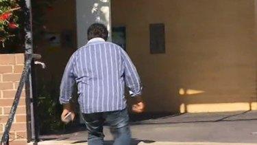 Mr Tripodi walks in to the police station.