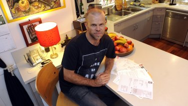 Russell Mills with a selection of his Origin Energy electricity bills.