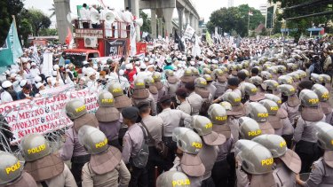 Supporters of the FPI face off with some of  the 2800 police who were brought in outside Indonesian police HQ in Jakarta.