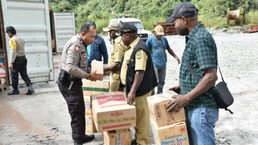 Police hand over food and supplies to local villagers from inside a mining area where there is conflict between the West Papua National Liberation Army and security forces.
