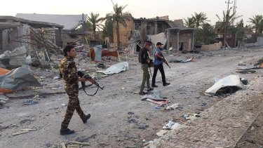 Iraqi security forces and tribal fighters walk down a street after regaining control of the northern neighborhoods of Ramadi.