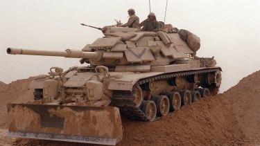 A tank negotiates a sand berm during an operation in the Gulf War.