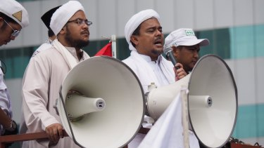Muhammad Rizieq Shihab, also known as Habib Rizieq, addresses protesters outside Indonesian police headquarters.