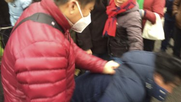 The plain-clothes officer throws Philip Wen to the ground.