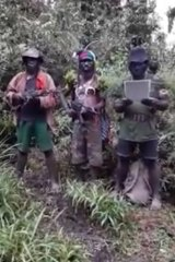 Self-styled West Papuan freedom fighters read out a statement in the jungle.