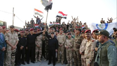 Iraq's prime minister Haider al-Abadi raises the national flag as he addresses forces  on the edge of Mosul's Old City.