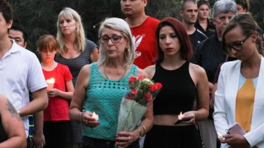 Residents and well-wishers pay their respects at a candelight vigil.