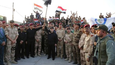 Iraq's Prime Minister Haider al-Abadi raises the national flag as he addresses forces in Mosul's Old City on Monday.