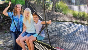 Vivienne Pearson and her two children, with the trampoline that cost them more than $4000, including accessories and garden landscaping.