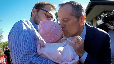Shorten kisses a baby after an announcement on Labor's gender equality policies at the Smith Park Kingsgrove Community Centre earlier this year.