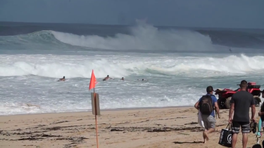 Rescuers, including Mick Fanning, rush to help the drowning surfer.