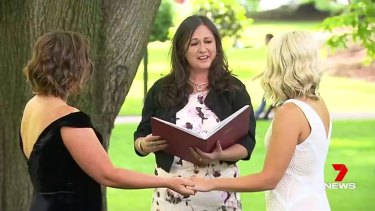 Celebrant Maria Aguilera (centre) officiates at the wedding of Amy and Elise McDonald in Carlton Gardens.
