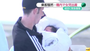 The father carries his newborn daughter off the plane.